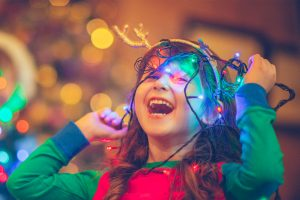 A young girl smiling while playing with Christmas lights