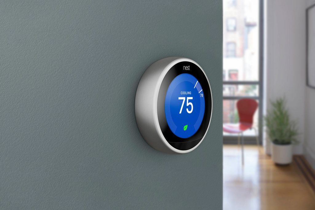 Nest thermostat on a wall that says cooling 75