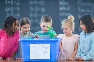 Five children placing plastic bottles in a blue recycling box