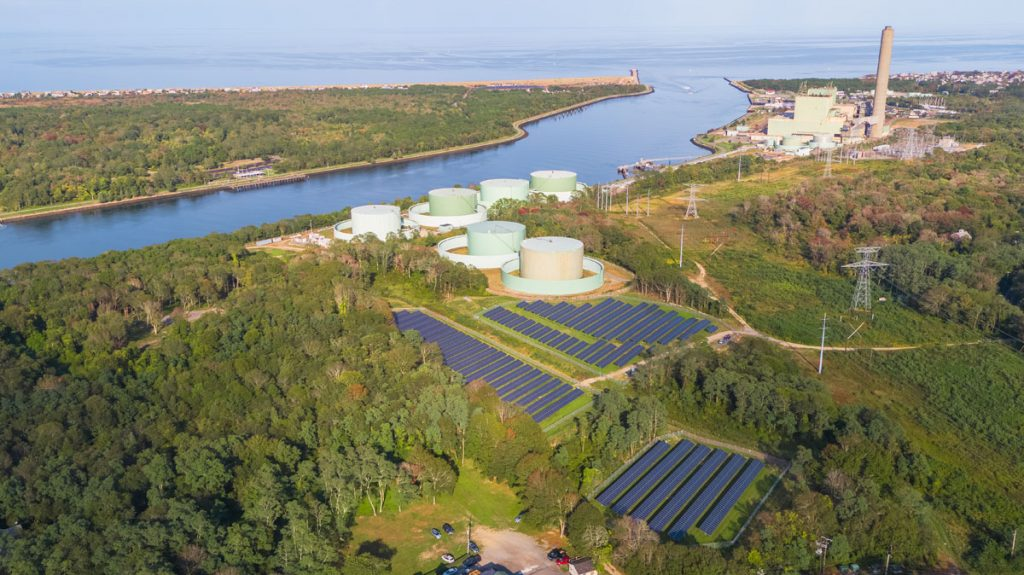 Community solar gardens next to water and industrial plants