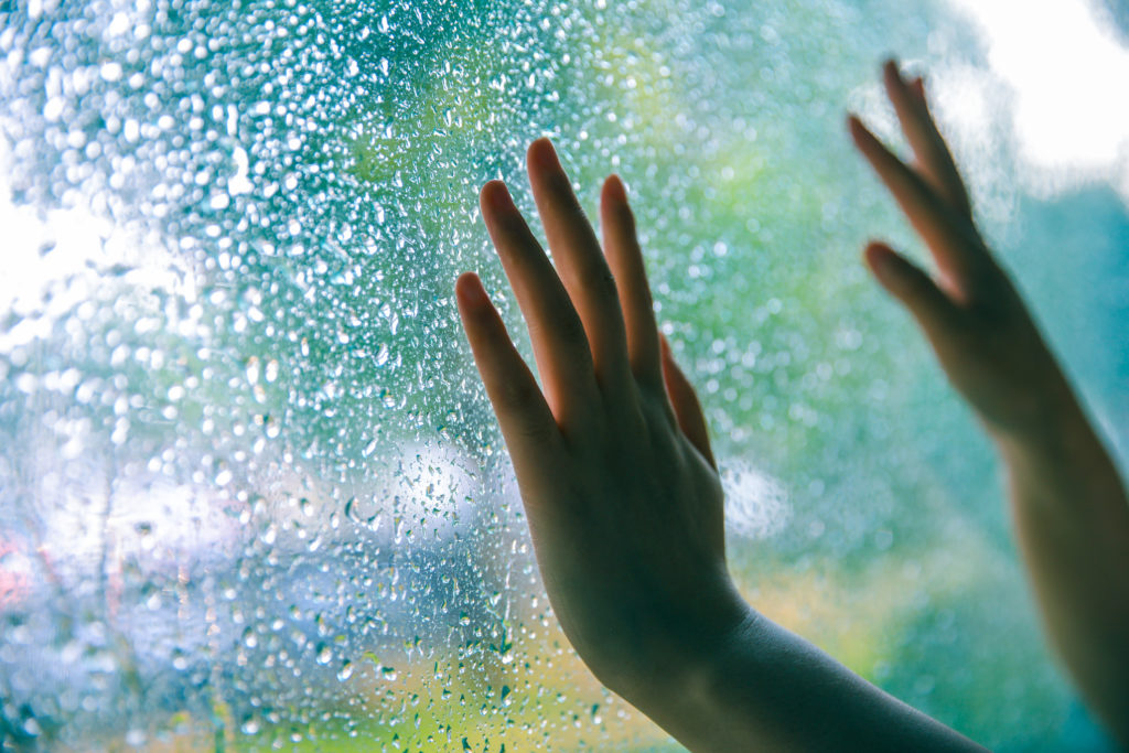 child's hands touching a window with water droplets