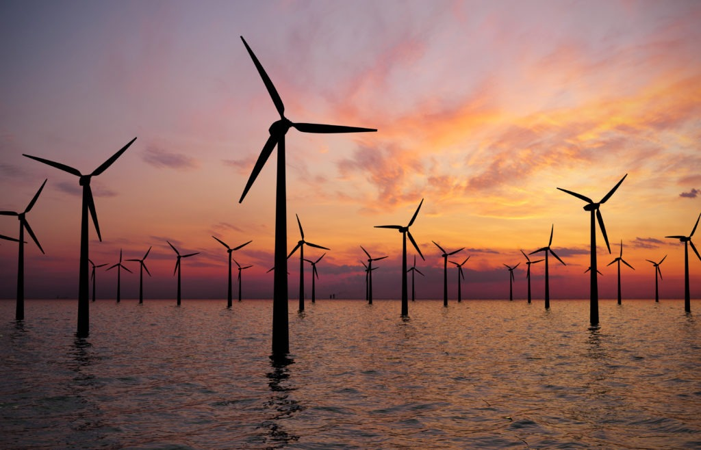 wind turbines in water against sunset